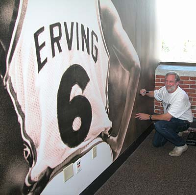 Larry Berman signing his photo of Julius Erving on the wall at Converse